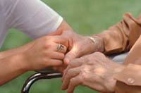 Picture of an elderly woman and younger woman holding hands